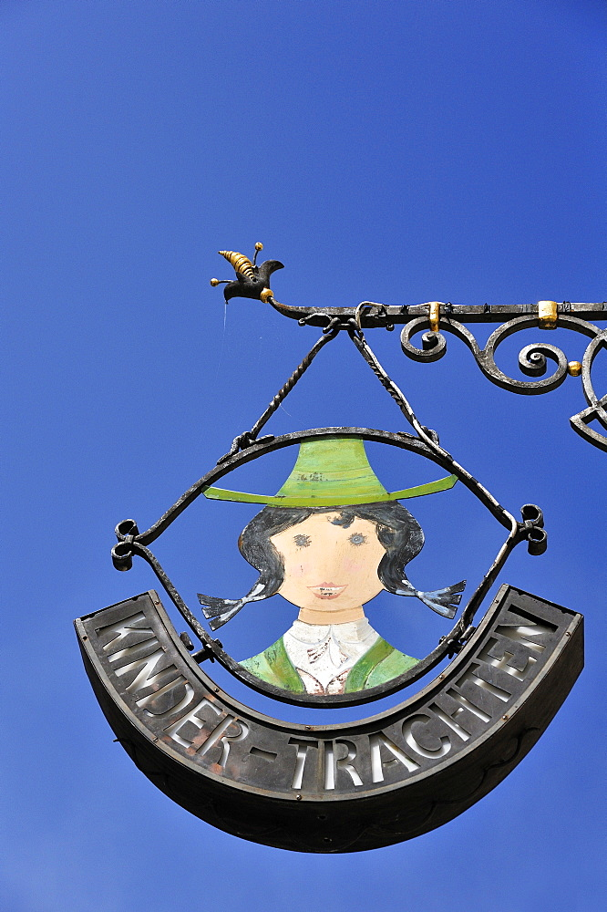Wrought iron hanging sign for a children's traditional costume shop, Universitaetsplatz square, Salzburg, Austria, Europe