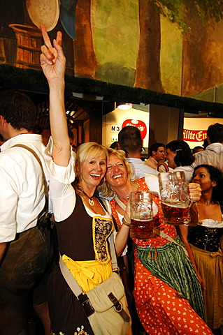 Women wearing traditional dress, called a Dirndl, dancing in the Beer Tent at the Oktoberfest Beer Festival or Wies\'n in Munich, Bavaria, Germany, Europe