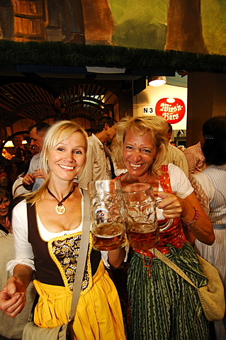 Women wearing a traditional dress, called a Dirndl, in a beer tent at the Oktoberfest Beer Festival or Wies\'n in Munich, Bavaria, Germany, Europe