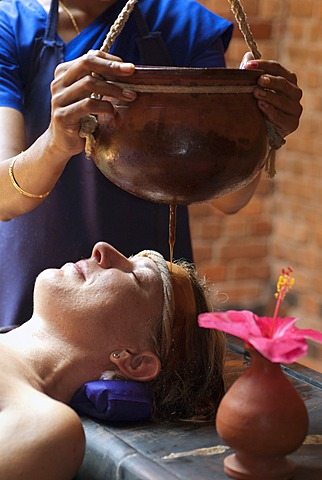 Woman receiving Ayurvedic treatment, Shirodhara, oil is gently poured over the forehead, Somatheeram Ayurvedic Health Resort, Chowara, Malabar Coast, South India, India, Asia