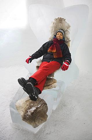 Tourist on an armchair made of ice, sitting on reindeer fur against the cold, Jukkasjaervi, Lappland, Northern Sweden