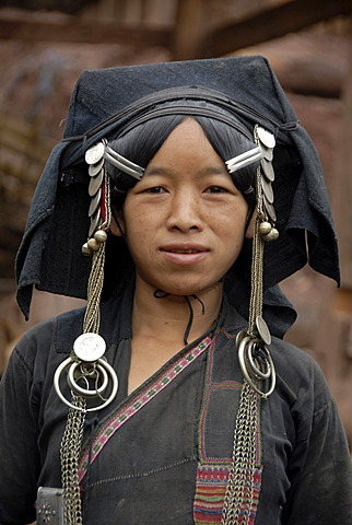 Portrait, ethnology, woman of the Akha Pixor ethnic group in traditional dress, hood as a headdress, wearing silver and coins as jewellery, village Ban Moxoxang, Phongsali district, Phongsali province, Phongsaly, Laos, Southeast Asia, Asia