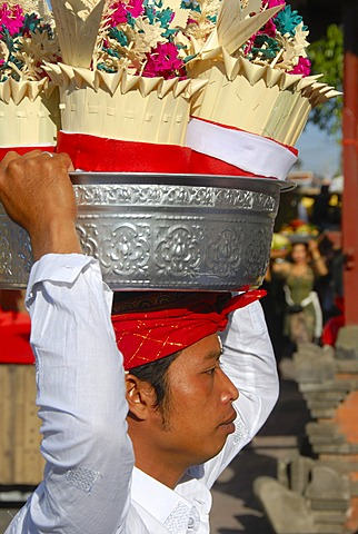 Balinese Hinduism, devout young man carrying a silver sacrificial bowl with gifts on his head, Pura Ulun Danu Batur temple, Batur village, Bali, Indonesia, Southeast Asia, Asia