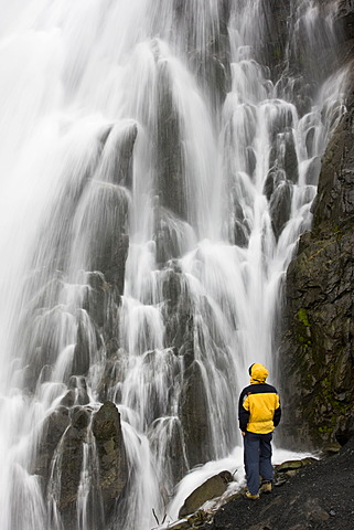 Waterfall with hiker near Seward, Alaska, USA