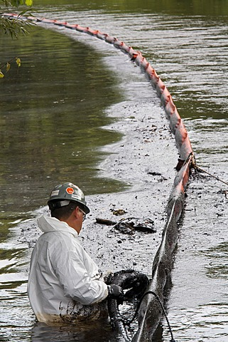 A worker vacuums oil from behind a containment boom on the Kalamazoo River during the cleanup of a major oil spil in which 800, 000 gallons of oil spilled from an Enbridge Energy Partners pipeline, Battle Creek, Michigan, USA