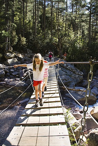 7-year-old girls on suspension bridge over Spasmiata river, Foret de Bonifatu, Corsica, France, Europe