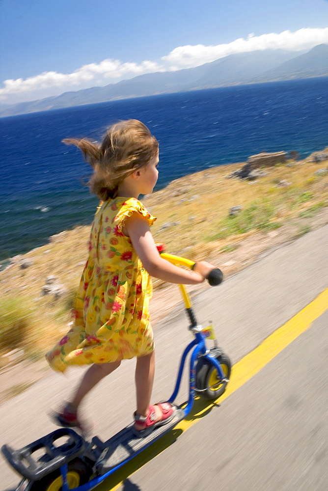 Child riding on its scooter at the coast, Peloponnese, Greece