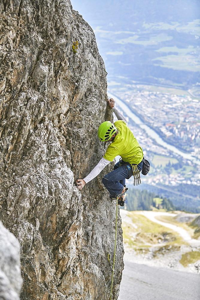 Climber with helmet climbing on a rock wall, behind Innsbruck, Northern Alps, Tyrol, Austria, Europe