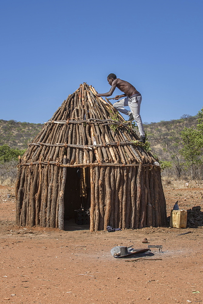 Man of the people of Ovahimba or Himba builds on the roof of a wooden hut, Kunene district, Namibia, Africa