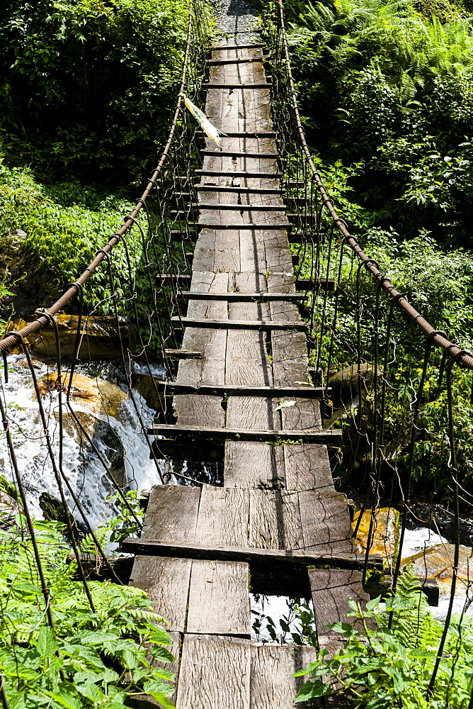 Old wooden suspension bridge across small river in Upper Modi Khola valley, Landruk, Kaski District, Nepal, Asia