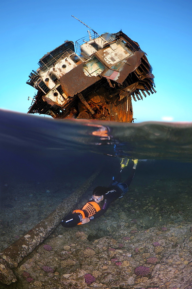 Freediver swims with underwater scooter near a shipwreck, Red Sea, Egypt, Africa - 832-381061