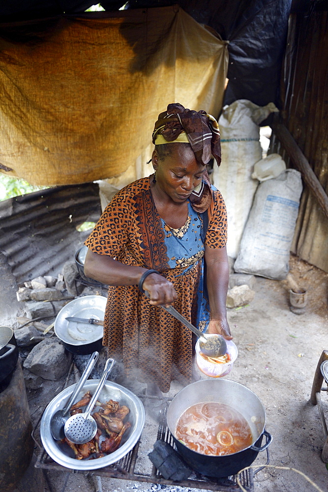 Woman is cooking in a simple kitchen, Riviere Froide, Ouest Department, Haiti, Central America