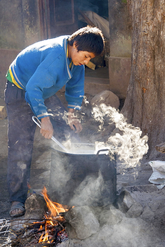 Boy preparing breakfast, open fire, boarding school, Potosi, Bolivia, South America