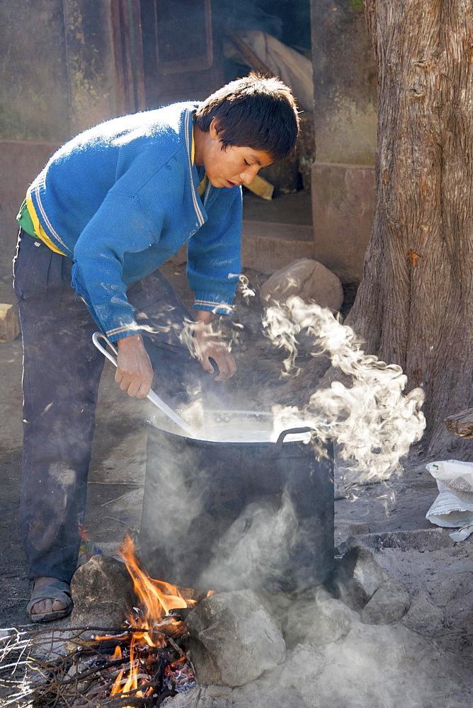 Boy preparing breakfast, open fire, boarding school, Potosi, Bolivia, South America