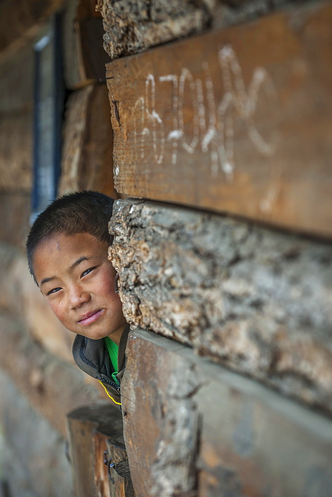 A boy looks out of a house, Wangue, Himalayas, Kingdom of Bhutan