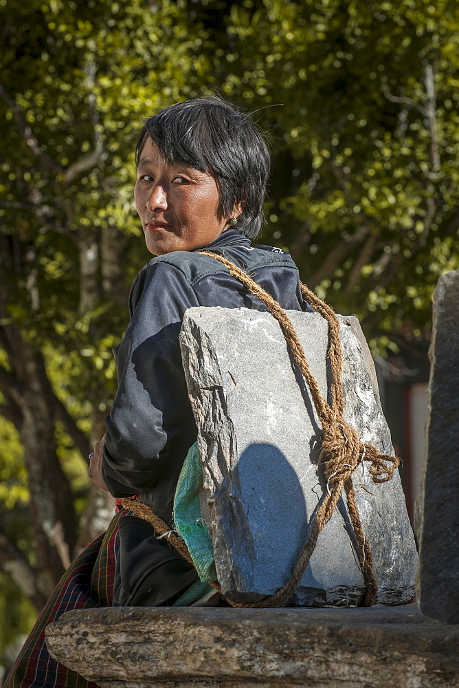 A woman taking a rest, with building materials, a stone slab on her back, Himalayas, Kingdom of Bhutan