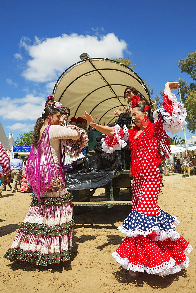 Women wearing colourful gypsy dresses dance the Sevillana, Pentecost pilgrimage of El Rocio, Huelva province, Andalusia, Spain, Europe