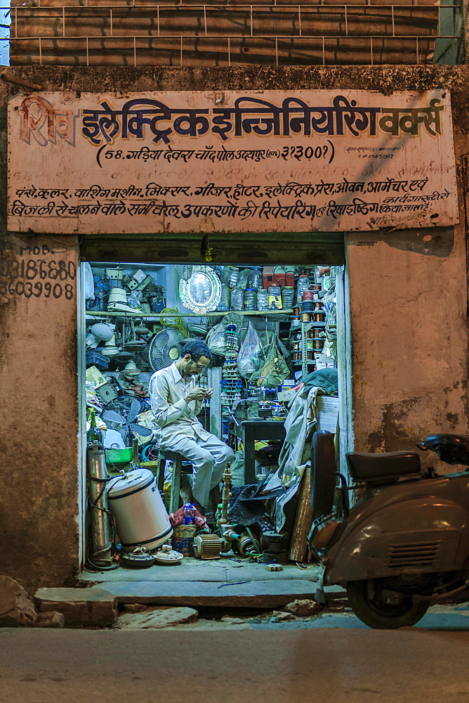 Electronics retailer in his workshop in the evening, Udaipur, Rajasthan, India, Asia