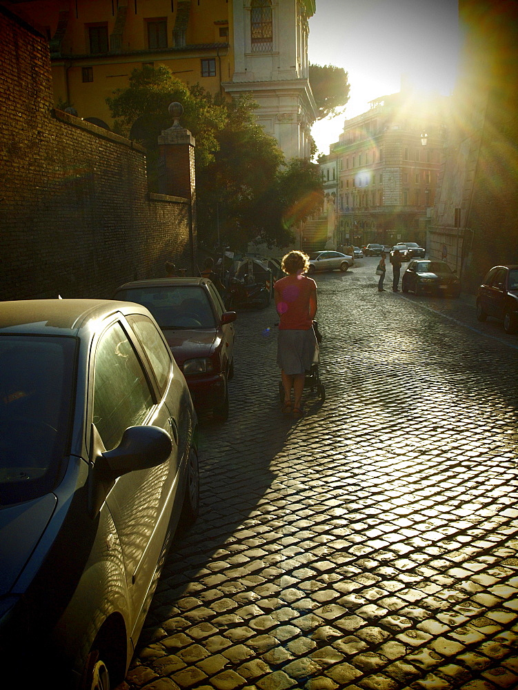 Woman backlit on an old cobblestone street in the evening, Rome, Italy, Europe