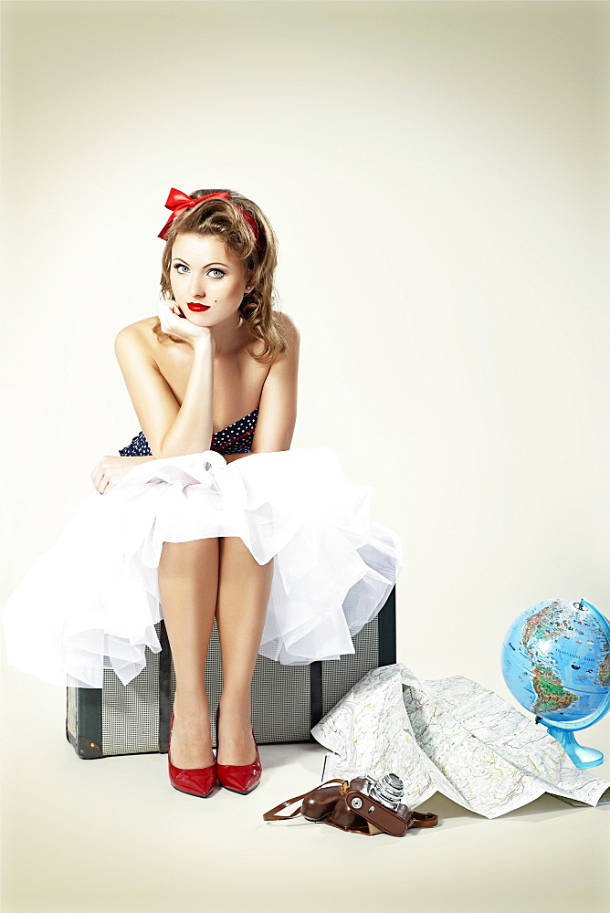 Young woman with red hair ribbon, sitting on an old suitcase, camera, map and globe spread in front of her, pin-up