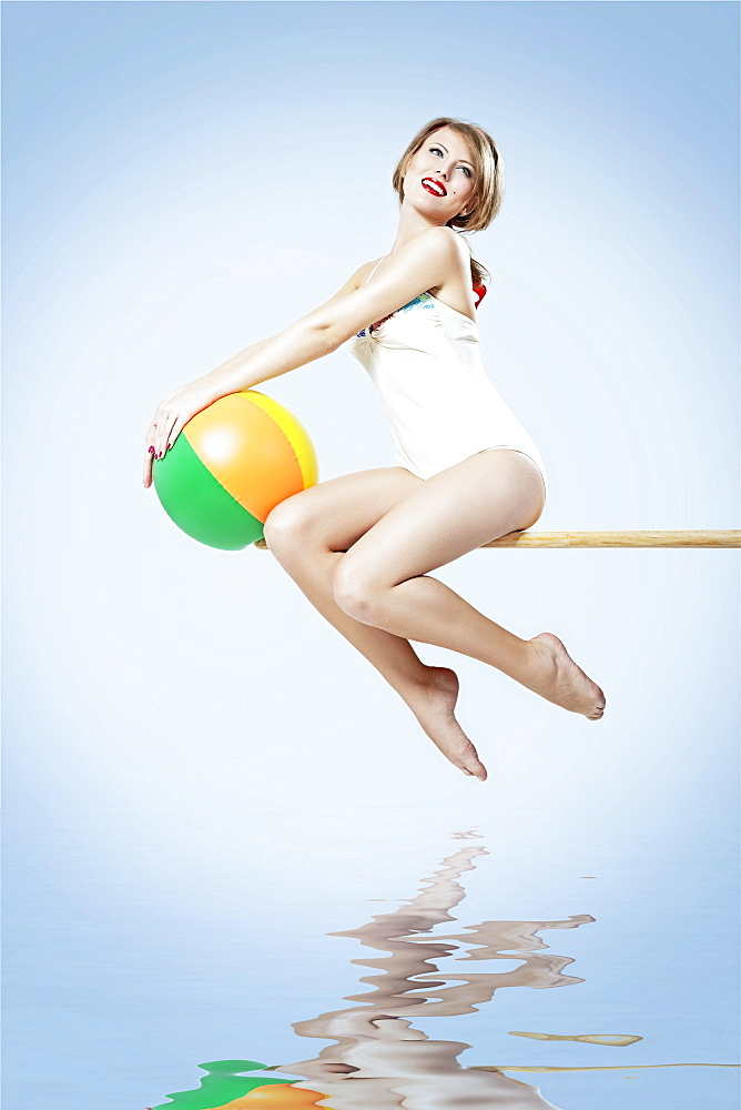 Young woman in a bright bathing suit sitting on a diving board and holding a beach ball, pin-up