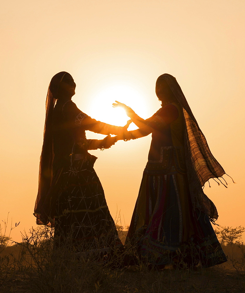 Two women in dresses dancing in front of the setting sun, Pushkar Camel Fair, Pushkar, Rajasthan, India, Asia