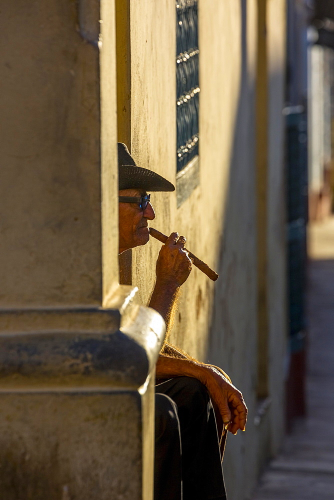 An elderly Cuban sitting on a doorstep in the evening light, smoking a cigar, Trinidad, Sancti Spiritus Province, Cuba, Central America