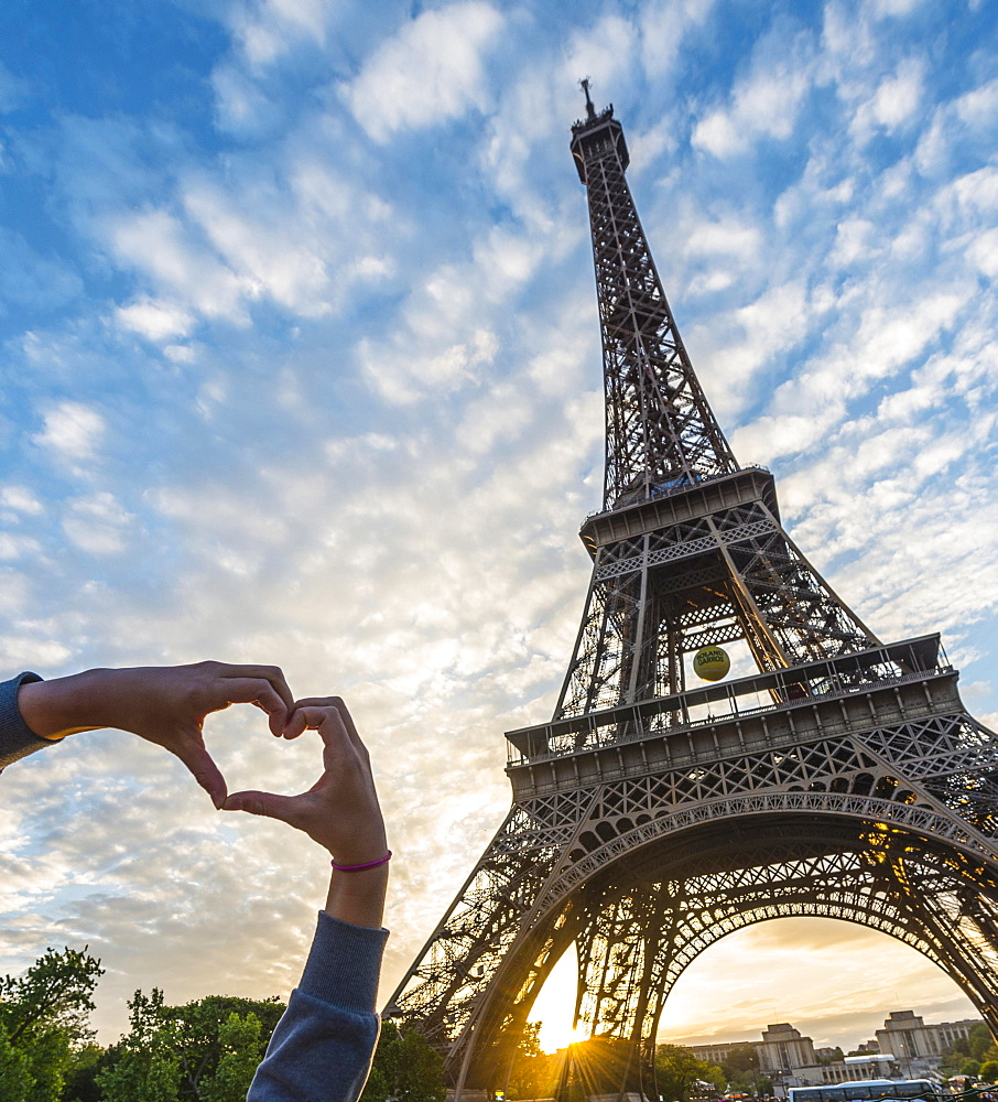 Hands forming heart, sunset behind Eiffel Tower, Champ de Mars, Paris, Ile-de-France, France, Europe