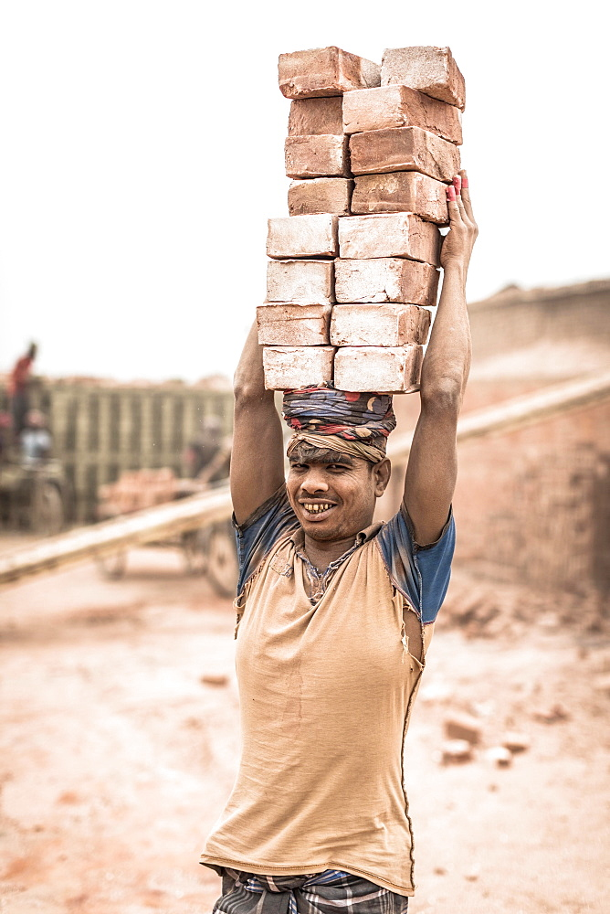 Worker with bricks on his head in the brickyard, Dhaka, Bangladesh, Asia