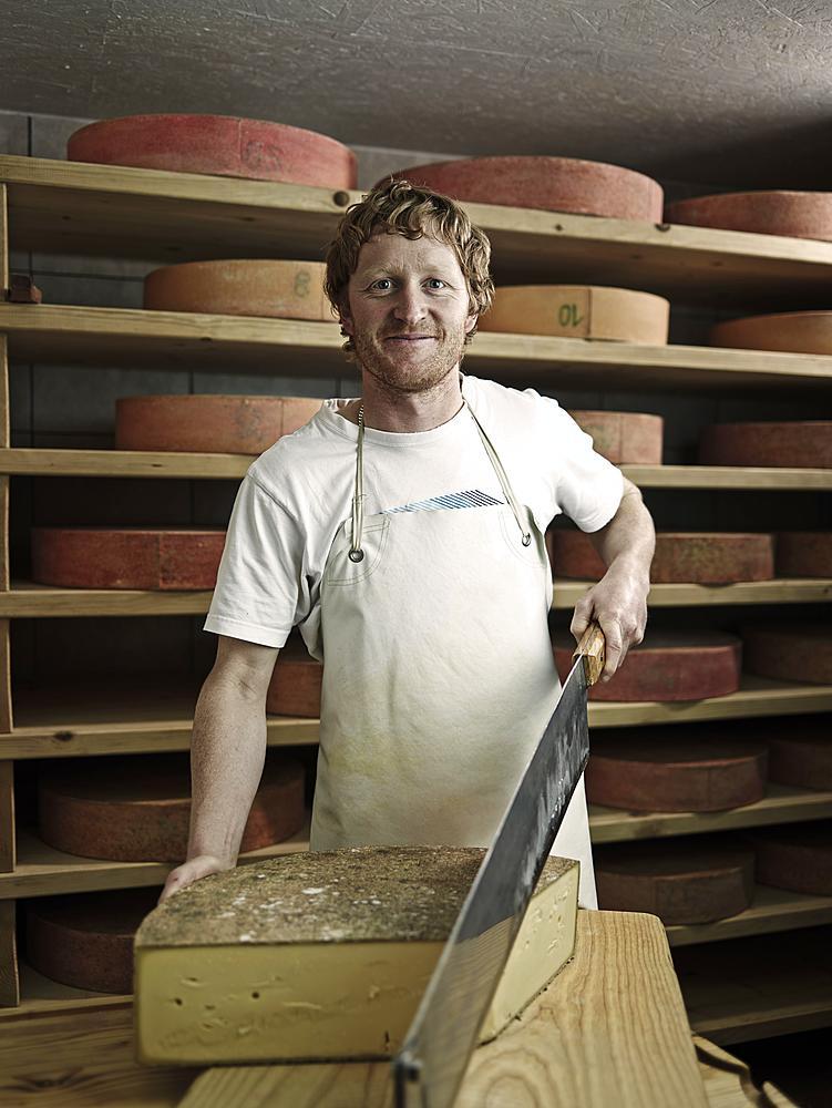 Dairyman cutting a mountain cheese, Steinbergalm, Inneralpbach, Alpbach, Tyrol, Austria, Europe