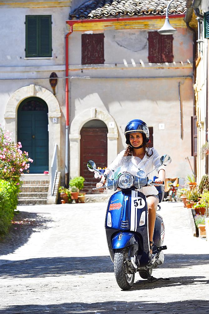 Woman on Vespa scooter, Piazza Tarsetti, Morro D'Alba, Marche, Italy, Europe