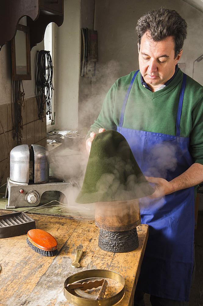 Man fitting wet hat body to wooden form, hatmaker workshop, Bad Aussee, Styria, Austria, Europe - 832-383780