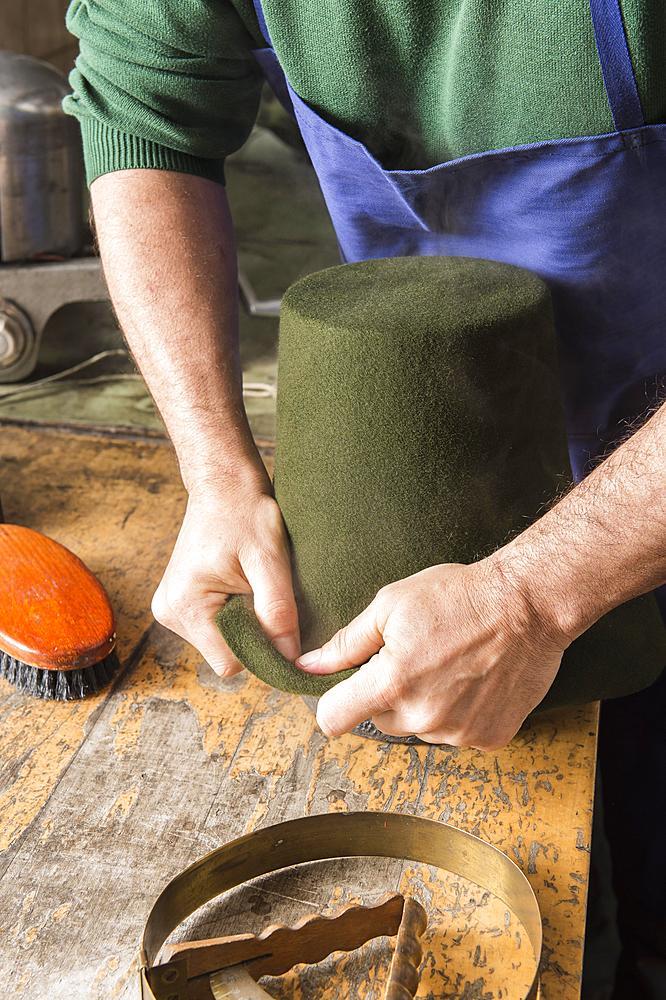 Man fitting wet hat body to wooden form, hatmaker workshop, Bad Aussee, Styria, Austria, Europe - 832-383784