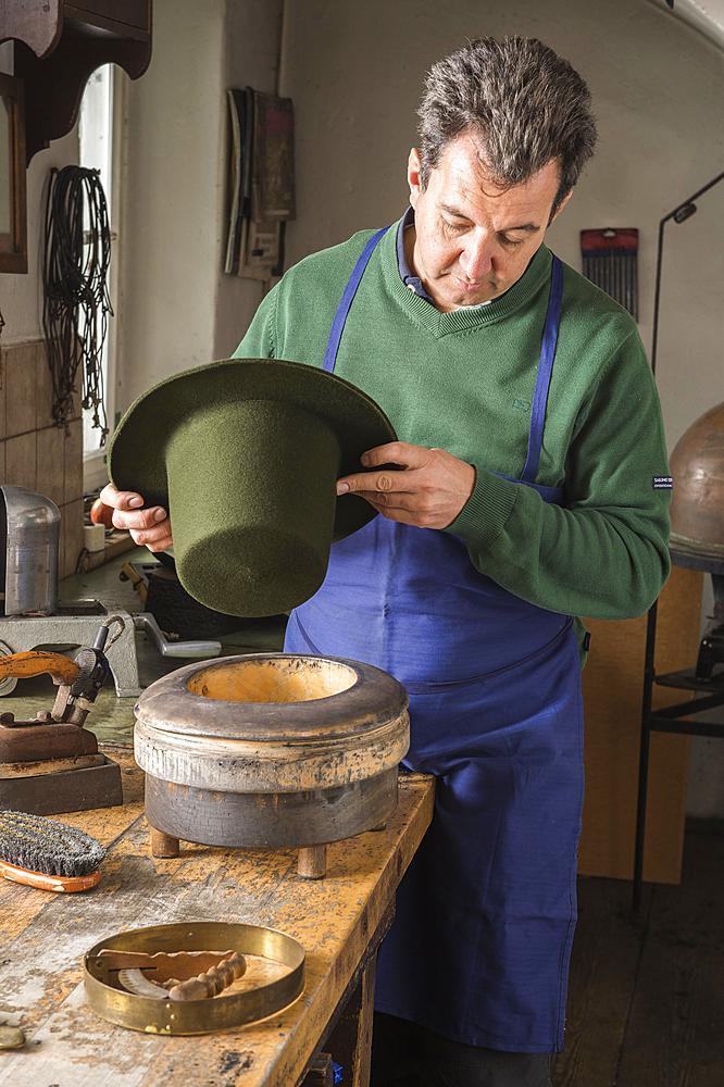 Hatter holding dry wool felt hat over an edge mold, hatmaker workshop, Bad Aussee, Styria, Austria, Europe - 832-383790