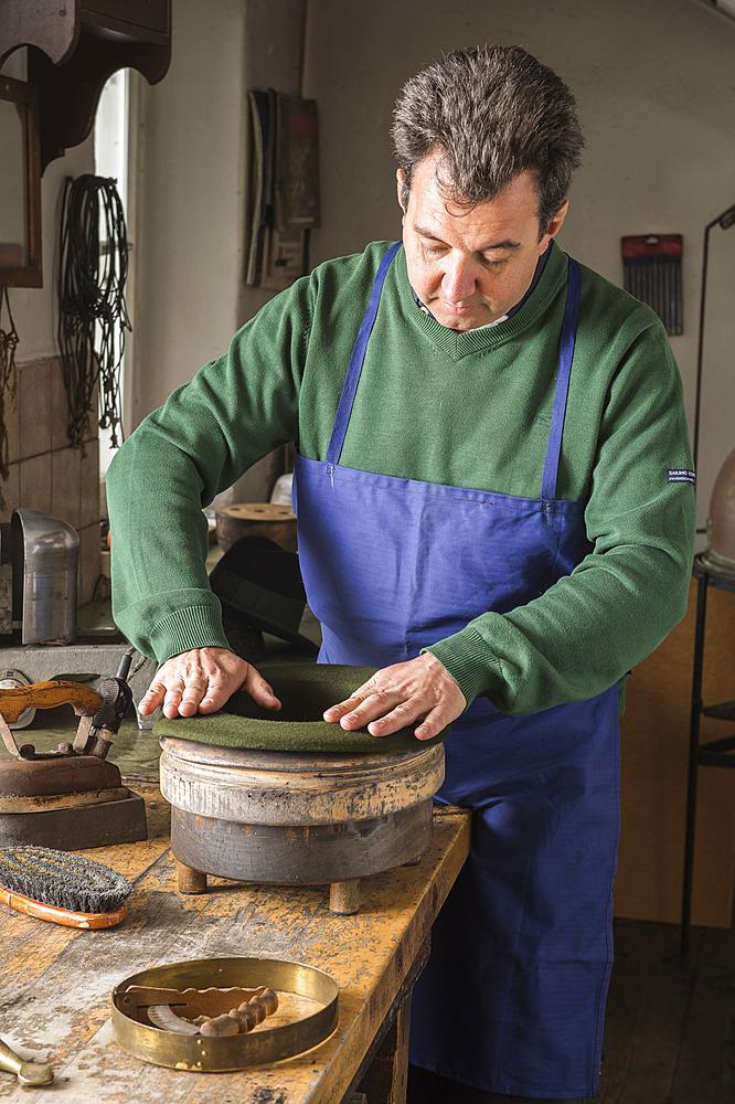 Hatter pushing dry wool felt hat into edge mold, hatmaker workshop, Bad Aussee, Styria, Austria, Europe - 832-383791