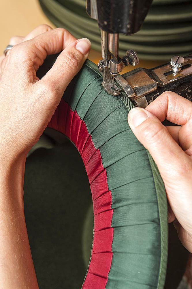 Hands sewing silk ribbon and inner lining on hat edge, hatmaker workshop, Bad Aussee, Styria, Austria, Europe - 832-383799