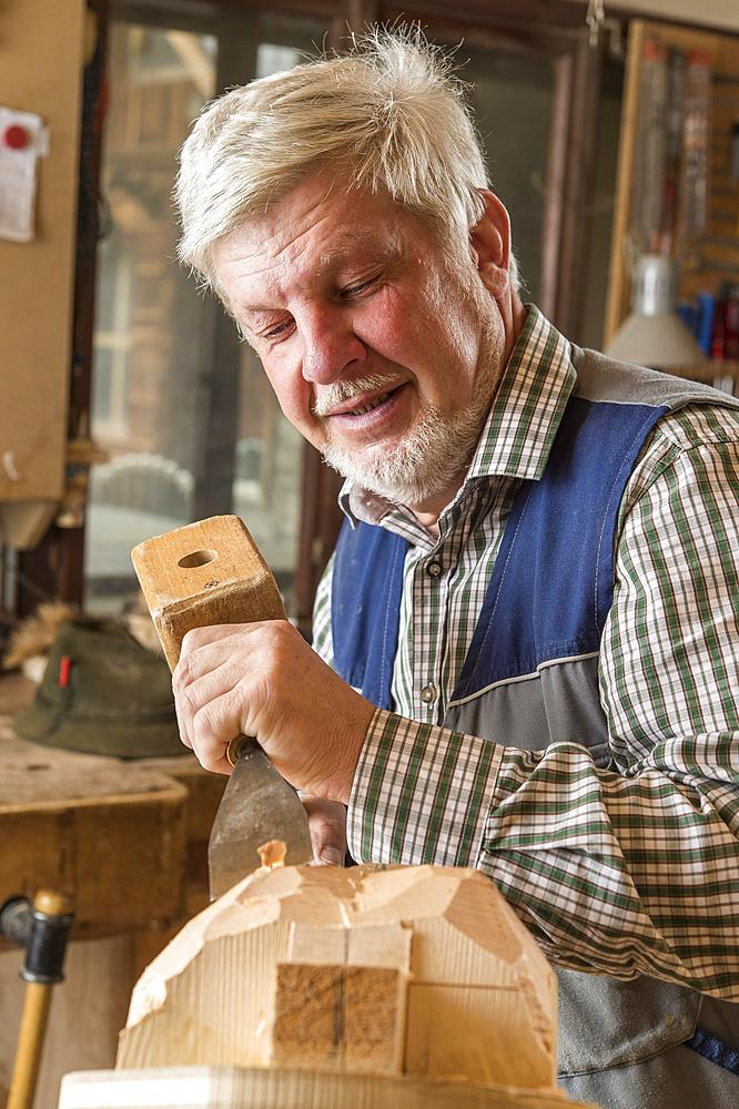 Wooden mask carver using wood carving tools on a wooden block, wooden mask, Bad Aussee, Styria, Austria, Europe