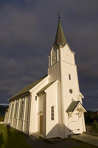 The white church of Eidet against dark clouds on the island of Langoya, Langoya, part of the archipelago of VesterÂlen, Vesteralen, Nordland, Norway, Europe
