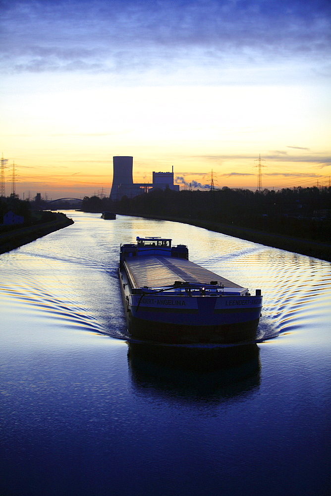 Cargo ship at dawn, Datteln-Hamm-Kanal, canal, near Waltrop, Trianel coal-fired power plant on Stummhafen at back, North Rhine-Westphalia, Germany, Europe