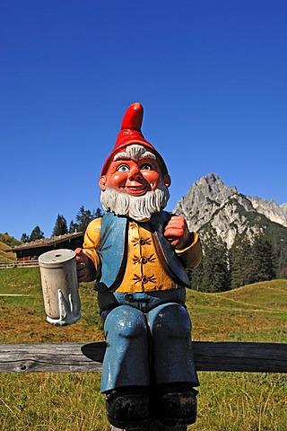 Garden gnome holding a beer mug on Litzlalm, alp, Mt Muehlsturzhoerner at back, Zell am See, Austria, Europe