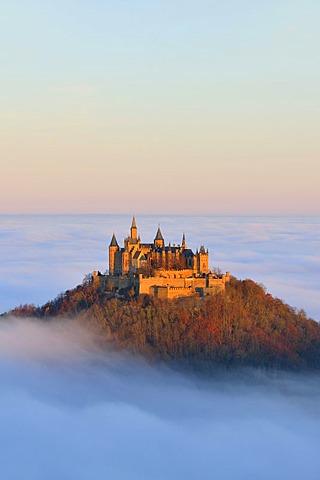 Burg Hohenzollern castle, in morning light, mist, with autumn forest, Schwaebische Alb, Swabian Alb, Baden-Wuerttemberg, Germany, Europe