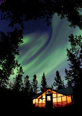 Illuminated wall tent, cabin with swirling Northern lights, Polar Aurorae, Aurora Borealis, green, near Whitehorse, Yukon Territory, Canada