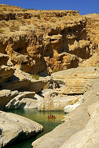 Tourists bathing in the stream in a narrow gorge in the Wadi Bani Khalid, Sultanate of Oman, Middle East