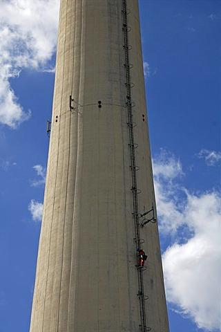 Chimney of Erlanger Stadtwerke heating plant, workman scaling chimney for repair works, Aussere Brucker Strasse 33, Elangen, Middle Franconia, Bavaria, Germany, Europe