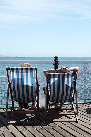 Couple relaxing in deckchairs, Brighton, Sussex, England, United Kingdom, Europe
