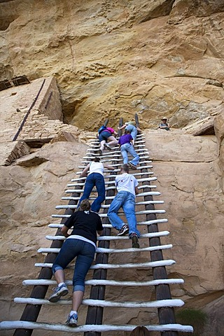 A park ranger watches as visitors climb a ladder to enter the Balcony House cliff dwelling at Mesa Verde National Park, featuring cliff dwellings of ancestral Puebloans that are nearly a thousand years old, Cortez, Colorado, USA