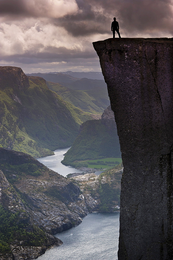 Man standing on Pulpit Rock, also known as Preikestolen, Lysefjorden fjord at the back, Jorpeland, Rogaland, Norway, Scandinavia, Northern Europe