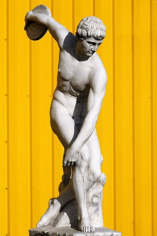 Sculpture of a Greek discus thrower, behind yellow metal panels, Herbolsheim, Baden-Wuerttemberg, Germany, Europe
