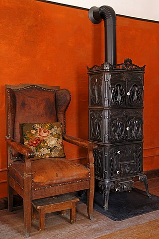 Fauteuil chair and cast-iron stove, 1900, living room in the teacher's apartment, school building from Pfaffenhofen, built in 1801, Franconian open-air museum, Eisweiherweg 1, Bad Windsheim, Middle Franconia, Bavaria, Germany, Europe