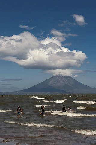 People walking on the shallow shore of Lago de Nicaragua, volcanic island of Ometepe and the stratovolcano Volcan Concepion at back, San Jorge, Nicaragua, Central America